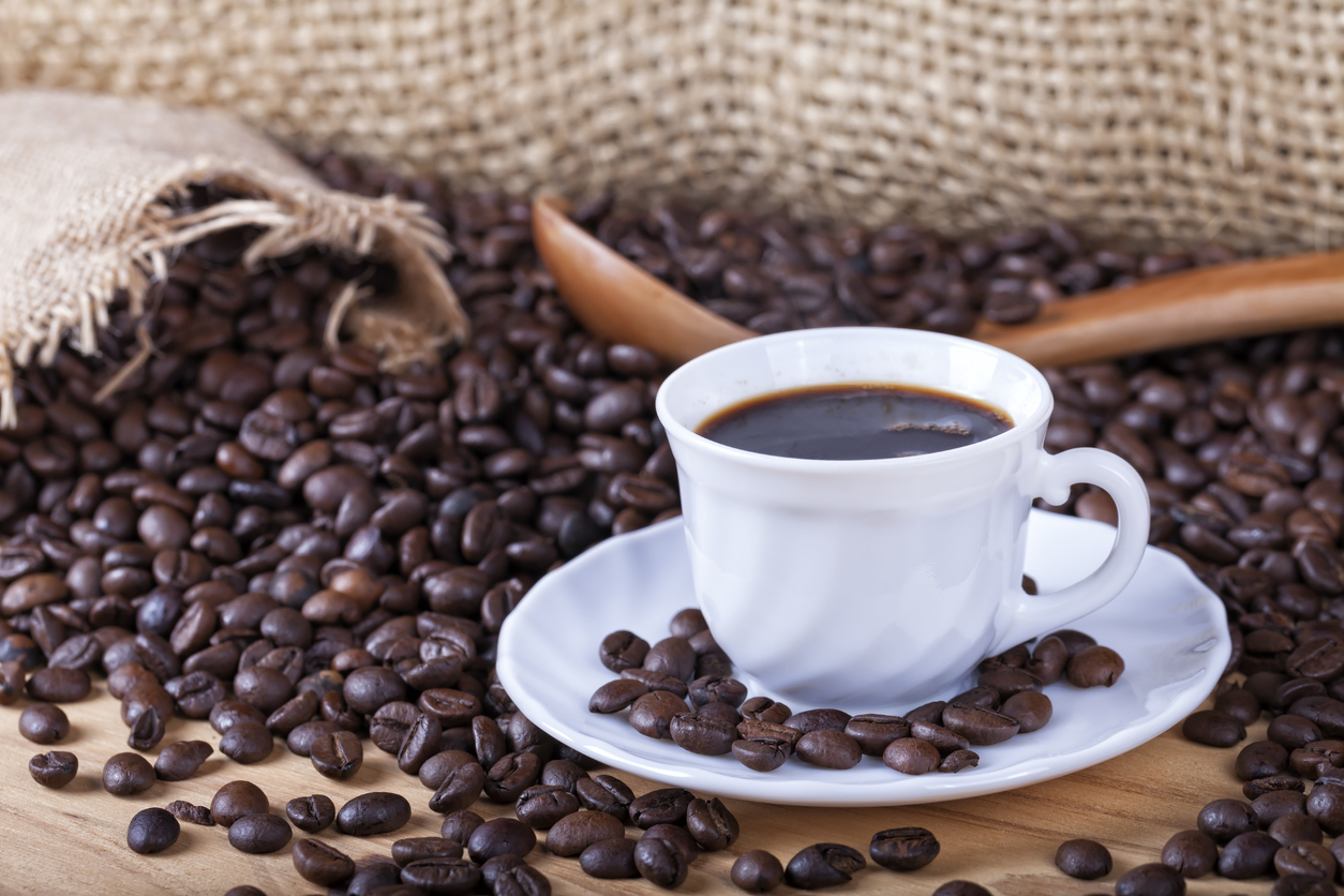 Une tasse de café avec des grains autour