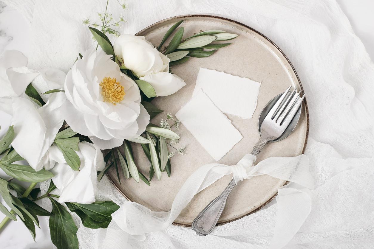 Une assiette en céramique avec des fleurs blanches dessus